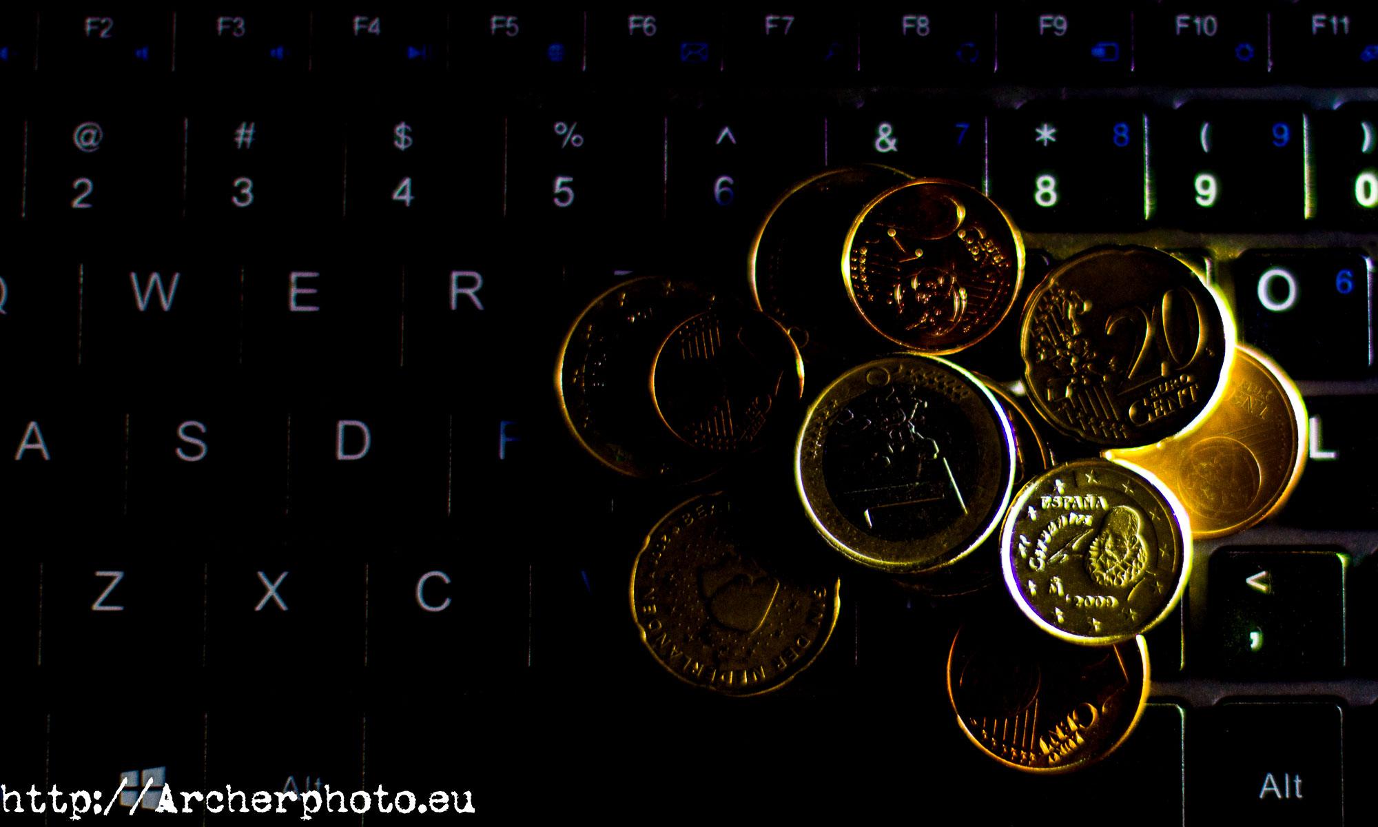 Tiendas web y fotografía comercial monedas sobre teclado, por Archerphoto fotógrafo profesional Valencia